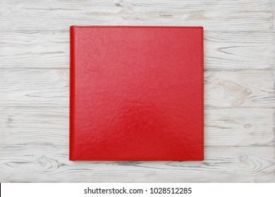 Photo book with embossing. Photo book on a light background. Family red photo book with  leather cover. Photoalbum with a hard cover on a wooden background. Wedding right red photo album.