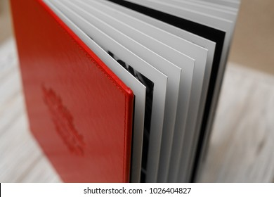 Photo book with embossing. Photobook on a light surface. Red photo book with  leather cover. Photoalbum with a hard cover on a wooden background. Bright red photo album. Photobook pages.