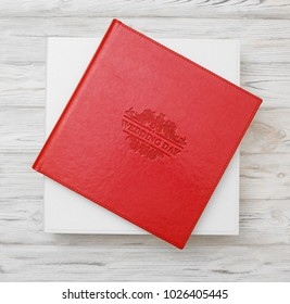 Photo book with embossing. Red photo book with  leather cover. Photo book with a hardcover on a wooden surface. Bright red photo album with a box.