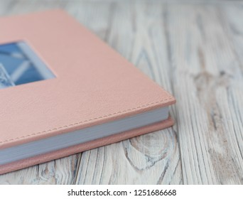 photo book with  leather cover Wedding photo album. pink photobook on a wooden background. sample photobook