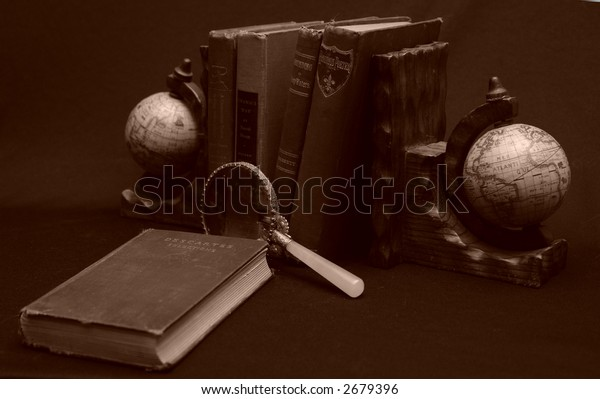 Photo of books with magnifying glass and world globes