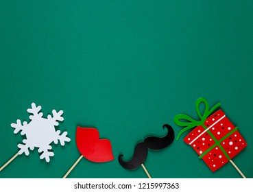 photo booth colorful props for christmas party - red lips, snowflake, gift, moustache on green background. Christmas and New year decorations