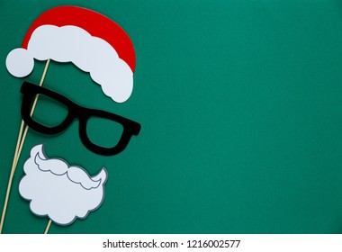 photo booth colorful props for christmas party - santa hat, glasses, beard on green background. Christmas and New year decorations