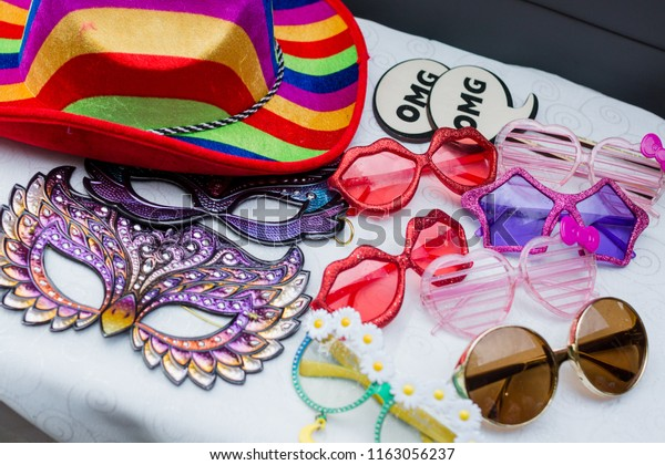 Photo booth props including funny glasses, masks, signs, and colorful hats.