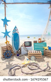 Photo booth setup on beach. Summer, surfing and fishing theme for an event party or birthday.