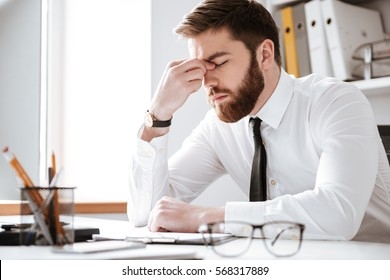 Photo of bored young businessman sitting in office near computer and glasses.