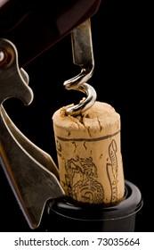 photo of bottle opener on black background pulling a cork outside of the bottle