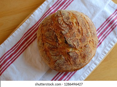 Photo of boule bread loaf on red and white tea towel and wooden table