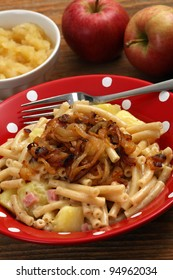 Photo of a bowl of Alplermagronen, or Alpine farmer's macaroni, a traditional Swiss meal made with noodles, potatoes, cheese, onions and served with applesauce.