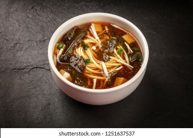 A photo of a bowl of miso soup with tofu, scallions, noodles, wakame, and enoki mushrooms, on a black background with a place for text