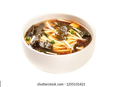 A photo of a bowl of miso soup with tofu, scallions, noodles, wakame, and enoki mushrooms, isolated on a white background with a clipping path