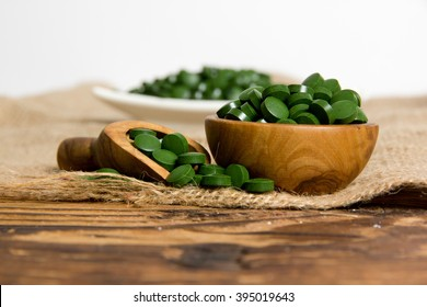 Photo of bowls and spoon full of chlorella pills on burlap with white space; concept of superfood