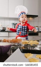 Photo of a boy in a chef hat and apron making cookies in the kitchen.