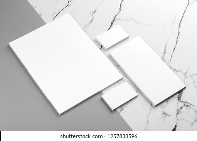 Photo of branding identity mock up on white marble and gray background. Mock up isolated on marble background