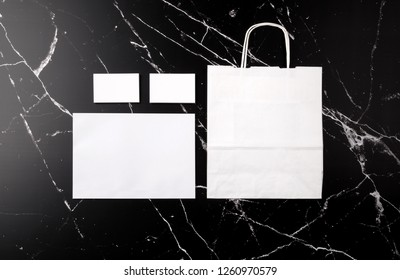 Photo of branding identity mock up on marble. Template isolated on marble background. White business cards, envelope and paper bag on black marble.