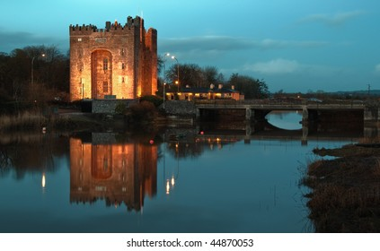 photo breathtaking bunratty castle in west of ireland at night with irish pub at night. famous european castle with water river reflection