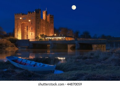 photo breathtaking bunratty castle in west of ireland at night. county clare. moon and river with boat. durty nelly irish pub, famous.