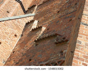 Photo of a brick wall in sun and shade with steps and small roofings at the cathedral in Bad Doberan in Mecklenburg-Vorpommern, Germany