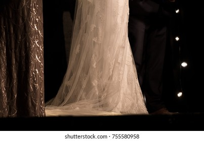 A photo of a bride's wedding gown flowing to the floor.