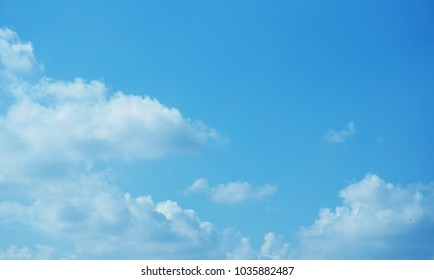 A photo of bright blue sky with fluffy white cloud on sunny day