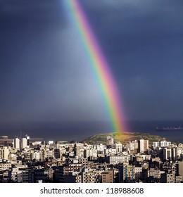 Photo of bright colorful rainbow over city, sun shining in rainy day, beautiful colors phenomenon in dark blue sky, overcast weather, nature landscape in the town, rain season