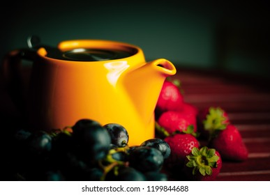 photo of a bright yellow teapot on a wooden table