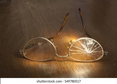photo of broken glasses on wooden background