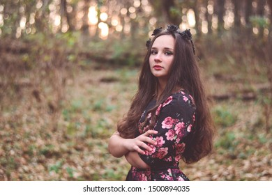 Photo of a brown haired girl in a black dress in a floral print with a black wreath with roses and thorns on her head in the forest in the evening in autumn