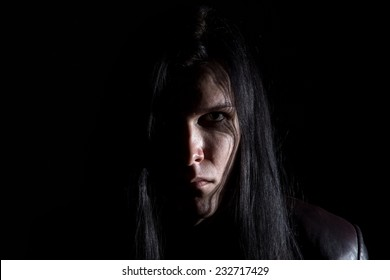 Photo of the brunet man with long hair on black background