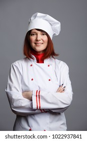 Photo of brunette chef in white robe and cap with arms crossed at waist