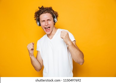 Photo of brunette joyous guy with curly hair listening to music via headphones and singing isolated over yellow background