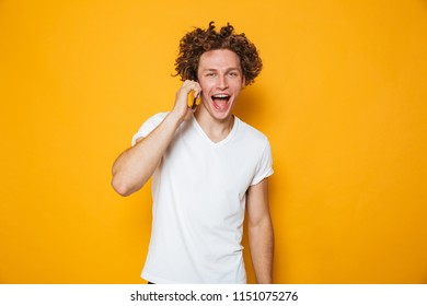 Photo of brunette joyous guy with curly hair talking on smartphone isolated over yellow background