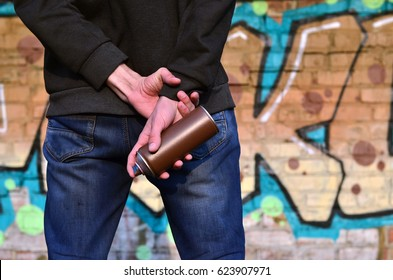 A photo of a bully who spoils state property, paints walls with aerosol paint. Fragment of the body of a young criminal vandal with a paint sprayer in a dirty hand. Problem of damage to property