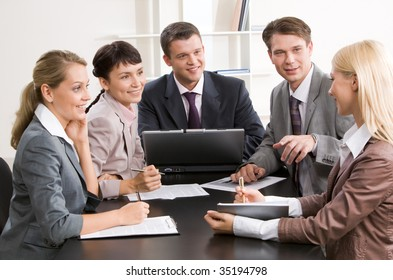 Photo of business group sitting at workplace and looking at successful woman