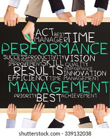 Photo of business hands holding blackboard and writing PERFORMANCE MANAGEMENT concept