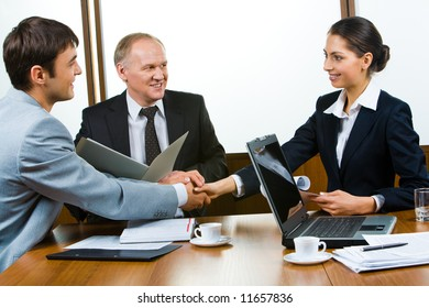 Photo of business partners holding hands making a consensus