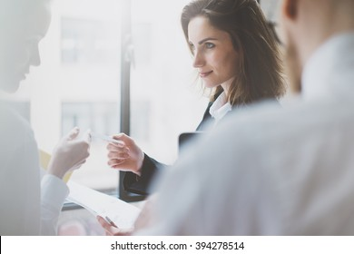 Photo business partners meeting. Team succes. Businesswoman giving businesS card colleague. Blurred background, film effect, horizontal