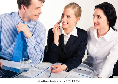 Photo of business partners working at meeting and looking at each other with smiles