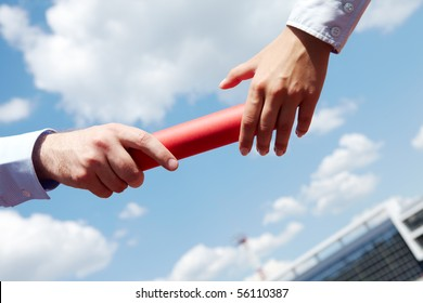 Photo of business people hands passing baton during marathon