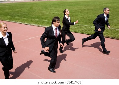 Photo of business people running on sport track