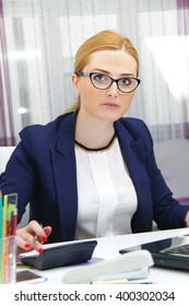 Photo of the Business woman analyzing investment charts with calculator and laptop