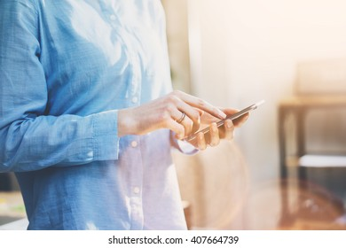 Photo business woman wearing jeans shirt, touching smartphone screen. Modern loft office. Blurred background. Horizontal mockup. Film effect