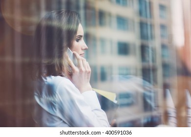 Photo business woman wearing modern suit, talking smartphone and holding papers in hands. Open space loft office. Panoramic windows background. Horizontal mockup. Film effect