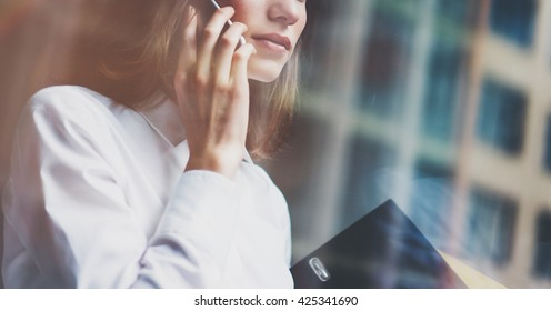 Photo business woman wearing modern suit, talking smartphone and holding documents in hands. Open space loft office. Panoramic windows background. Horizontal mockup. Film, flare effect.