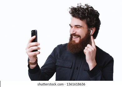 Photo of businessman in dark shirt talking on phone with airpods over white background