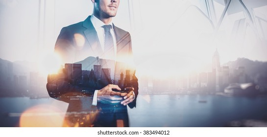 Photo of businessman holding smart phone. Double exposure photo of panoramic city view at sunrise