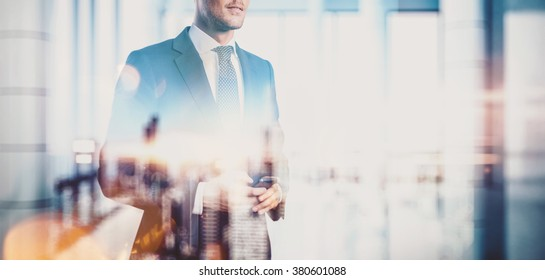 Photo of  businessman holding smartphone. Double exposure, city on the background. Blurred background
