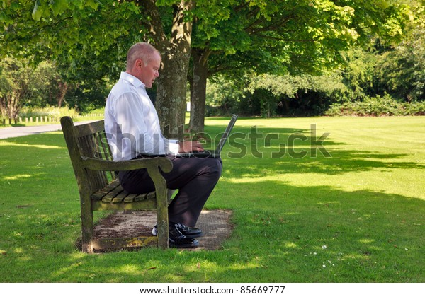 Photo of a businessman in smart casual clothing sat on a park bench working on his laptop computer.