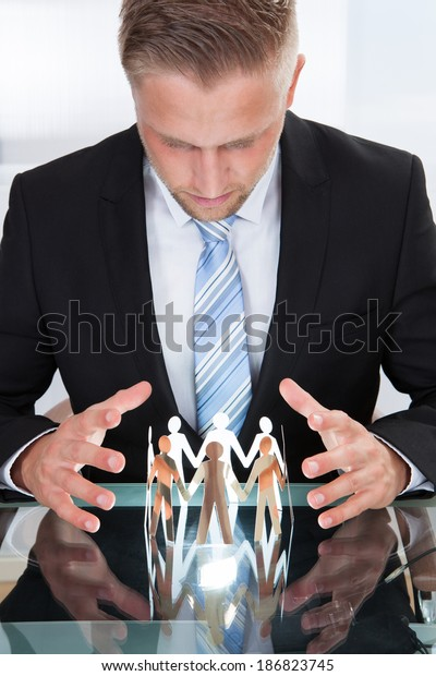 Photo Of Businessman Taking Care Of Paper People