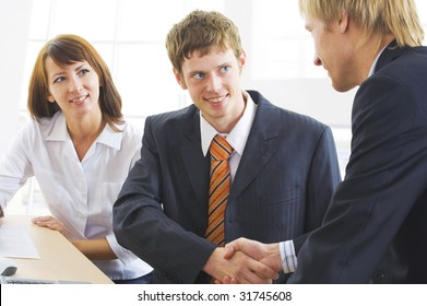Photo of businessmen  handshaking with woman near by